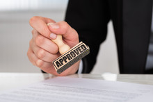 Businesswoman Stamping Approved On Contract Paper At Desk
