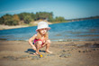 Adorable toddler girl playing with beach toys on white sand beach.