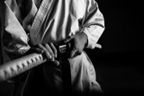 Close up of young martial arts fighter with katana siting in seiza position, black and white.