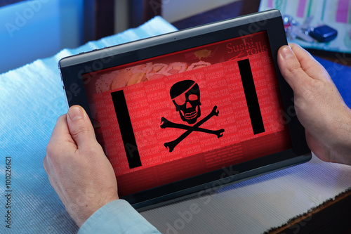 Fototapeta  hands of a man consulting in touchscreen a hacked website /man with tablet at ho