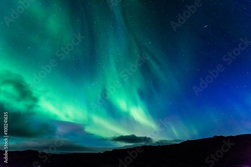 Photo Stands Northern lights Aurora at night over the land as a background