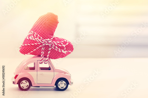 Fotobehang Vintage cars Miniature car carrying red heart cushion