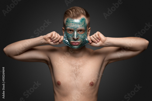 Fotografie, Tablou  Peeling off / Portrait of a beautiful young man peeling off a facial mask, face and body skin care retreat