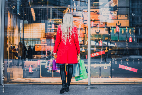 Woman looking at window shop - Young pretty girl standing in front of a boutique Fototapeta