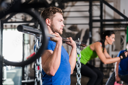 fototapeta na szkło Mann im Fitnessstudio bei Functional Fitness Sport mit Hantel und Kette