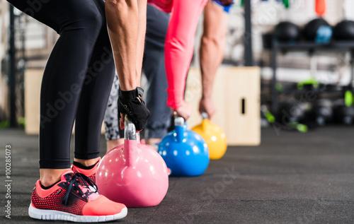 fototapeta na szkło Gruppe beim functional Fitness Training mit Kettlebell im Sport Studio