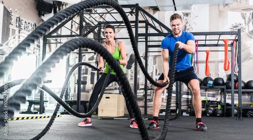 fototapeta na szkło Frau und Mann im Fitnessstudio mit battle rope