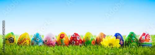 Colorful hand painted Easter eggs on grass. Banner, panoramic Canvas Print
