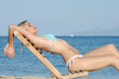 Blonde woman with exelent slim body wear bikini lying on a wooden beach chair, sea and sky as background