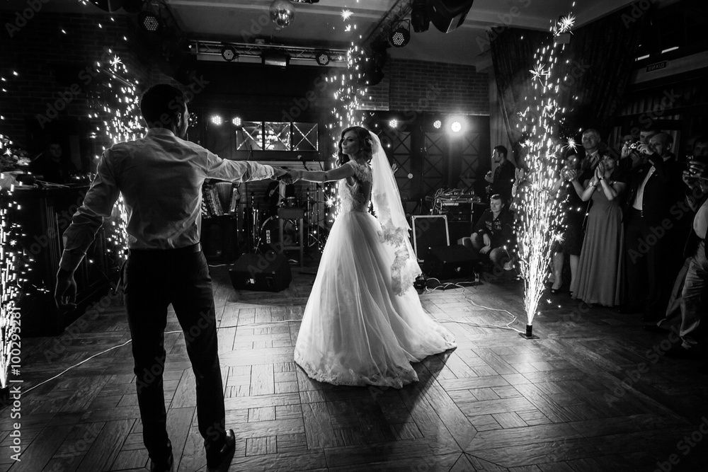 Fototapeta Beautiful newlywed couple first dance at wedding reception surrounded by smoke and lights and sparks b&w