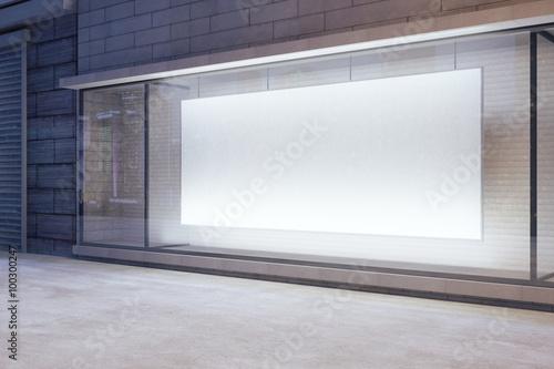 Large blank banner in a shop window at night, mock up Fototapeta