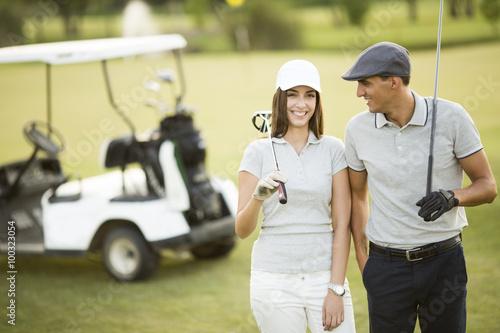 Young couple at golf cart - 100323054