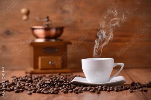 Fotografia  tazza di caffè fumante con macinino sullo sfondo