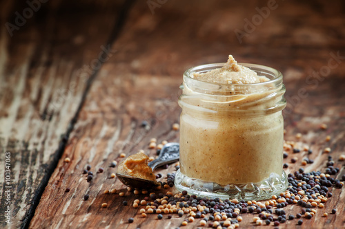 Photo  Freshly prepared mustard sauce in a small glass jar with a spoon