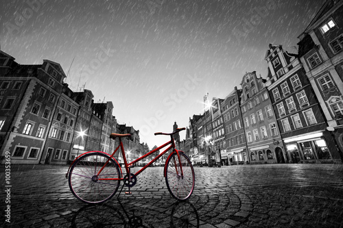 Fototapeta Vintage red bike on cobblestone historic old town in rain. Wroclaw, Poland.