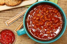 Bowl Of Baked Beans And Ketchup At Table