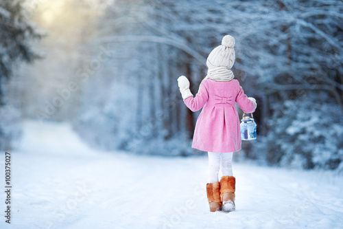 Adorable girl with lamp and candle in winter on Xmas eve outdoors Poster