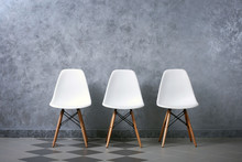 Three White Chairs On A Grey W...