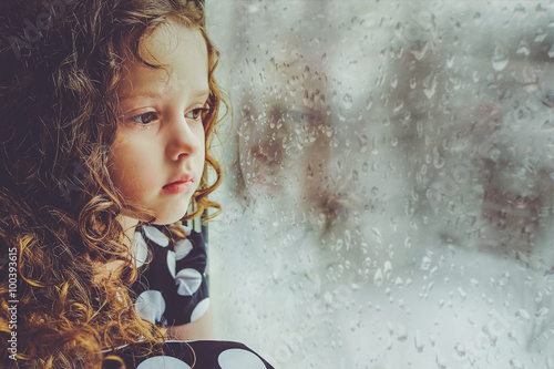 Sad child looking out the window. Toning photo. Fototapeta