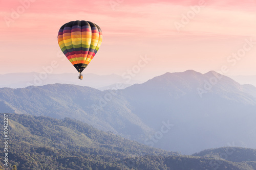 Fototapeta Hot air balloon above high mountain at sunset