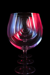 Fototapeta Koktajle Party wine glasses in nightclub lit by red, blue, lilac lights, nightlife and entertainment industry, objects in row isolated on black background