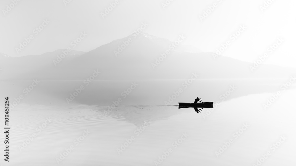 Fototapeta Fog over the lake. Silhouette of mountains in the background. The man floats in a boat with a paddle. Black and white