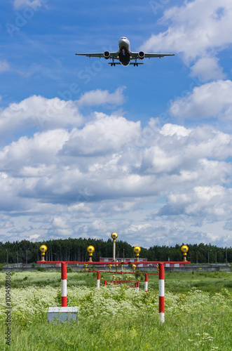 Landing jet airplane over runway approach lights - Buy this