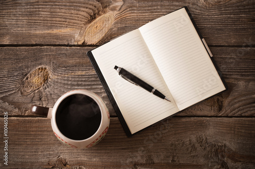Fotografie, Tablou  notebook with pen and coffee on old wooden table