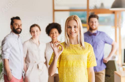Valokuva  happy woman showing ok over creative office team