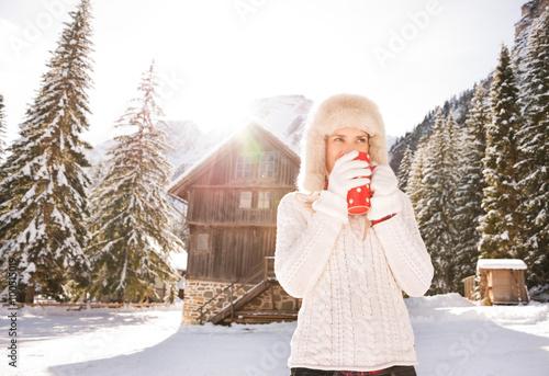 Fényképezés  Woman in white sweater enjoying hot beverage near mountain house