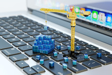 Designing, Engineering, Business Planning And Project Development, Computer Technology Concept, Construction Crane On Laptop Keyboard Assembles Abstract Blue Blocks