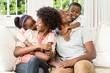 Leinwandbild Motiv Smiling family sitting on the couch together