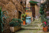 Fototapeta Fototapety na drzwi - old traditional italian courtyard with stone stairs and potted plants in a small medieval town of Sorano in Tuscany