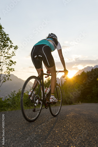 cyclist from behind with sunset Poster