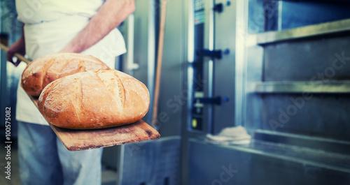 Staande foto Bakkerij Bäcker mit Brot in Bäckerei auf Schaufel steht vor dem Backofen