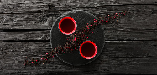 FototapetaCups of tea on slate plate on a black wooden table