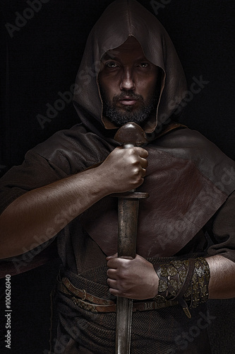 Stampa su Tela Viking warrior with sword over black background holding sword