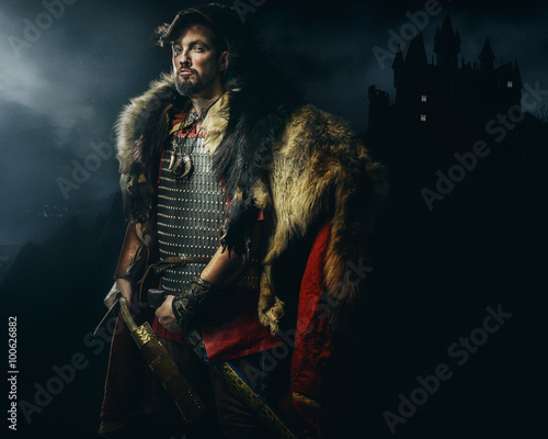Foto  Viking warrior, male dressed in Barbarian style with sword, bear