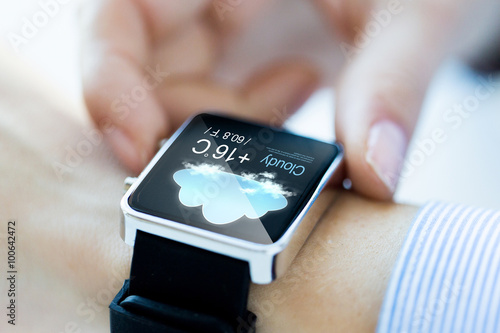 Fototapeta  close up of hands with weather icon on smartwatch