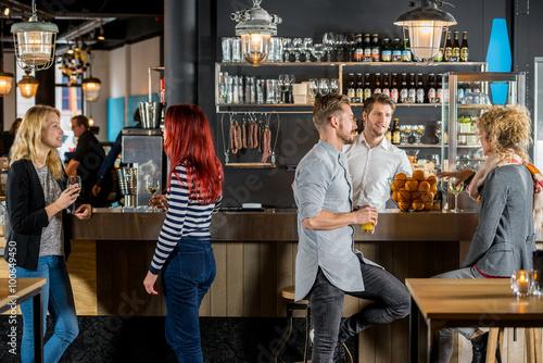 Friends Talking While Having Their Drinks In Bar Fotobehang