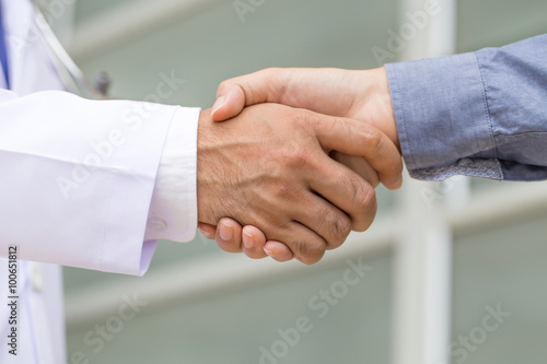 Doctor shakes hands with a patient Poster