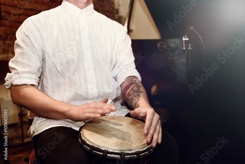 Obraz na plátne stylish percussionist playing on leather drum on a concert, hand
