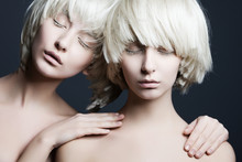 Portrait Of Two Beautiful Girls Twins With Closed Eyes In Studio