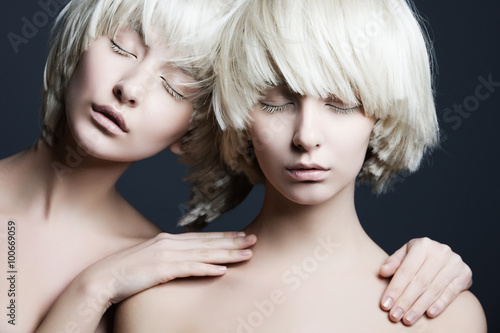 Photo  Portrait of two beautiful girls twins with closed eyes in studio