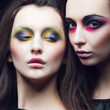 Portrait of two beautiful young girls twins in the studio with bright makeup on a black background, the concept of beauty