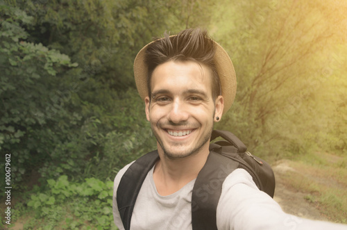 Fotografía Handsome guy is taking a selfie with his smartphone in the nature - people, tech