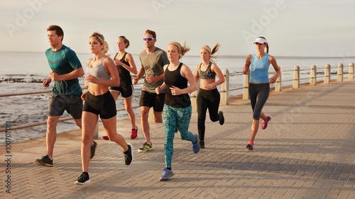 Fotografie, Obraz  Young people running along beach boardwalk