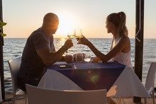 Couple Watching Sunset Dining In Sea Restaurant