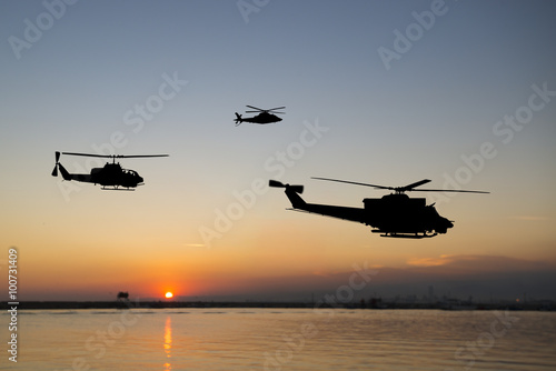 Türaufkleber Hubschrauber Three flying army helicopters on sunset background
