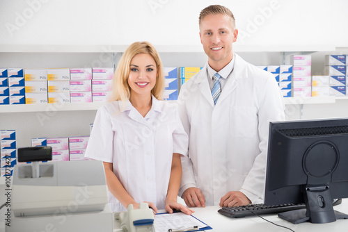 Pharmacists Smiling At Counter In Pharmacy Poster